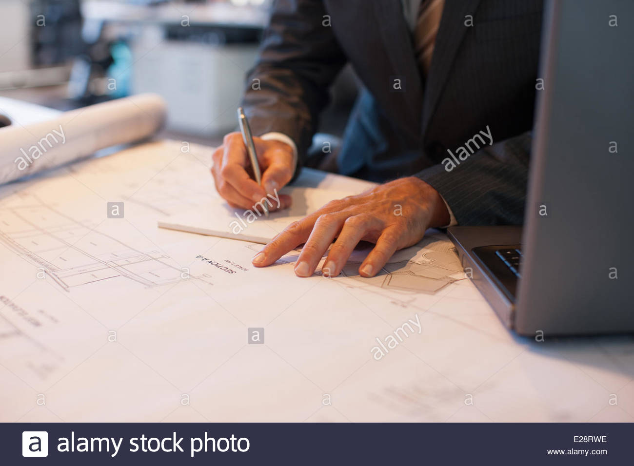 Businessman working on blueprints in office - Stock Image