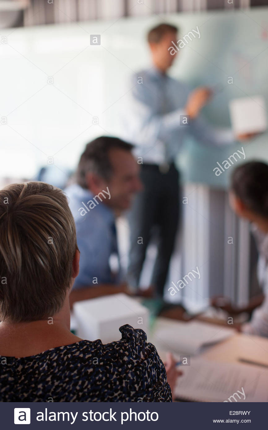 Businessman holding cube talking to co-workers in conference room - Stock Image