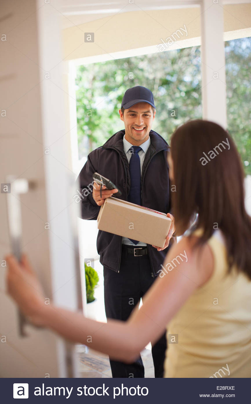Delivery man handing box to woman - Stock Image