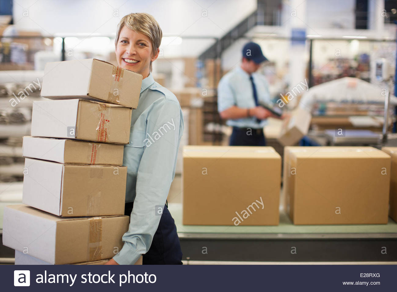 Worker carrying boxes in shipping area - Stock Image