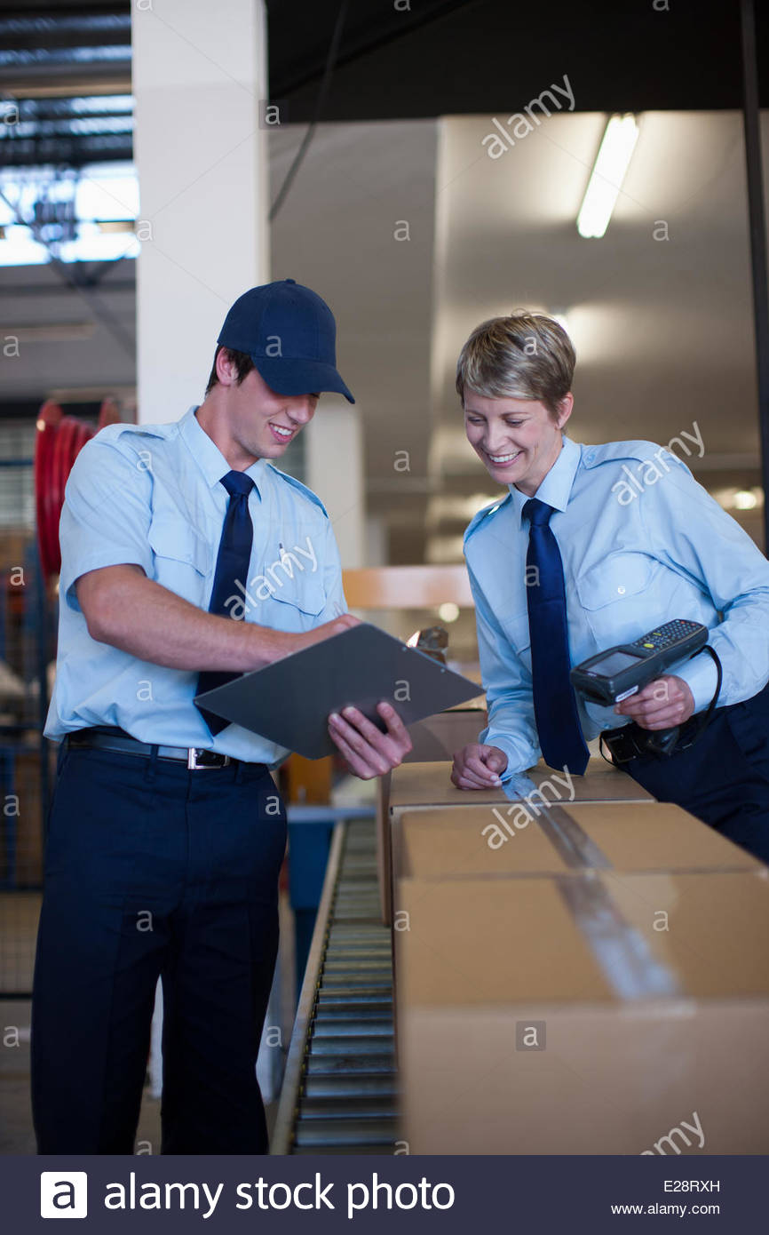 Workers standing together near box on conveyor belt - Stock Image