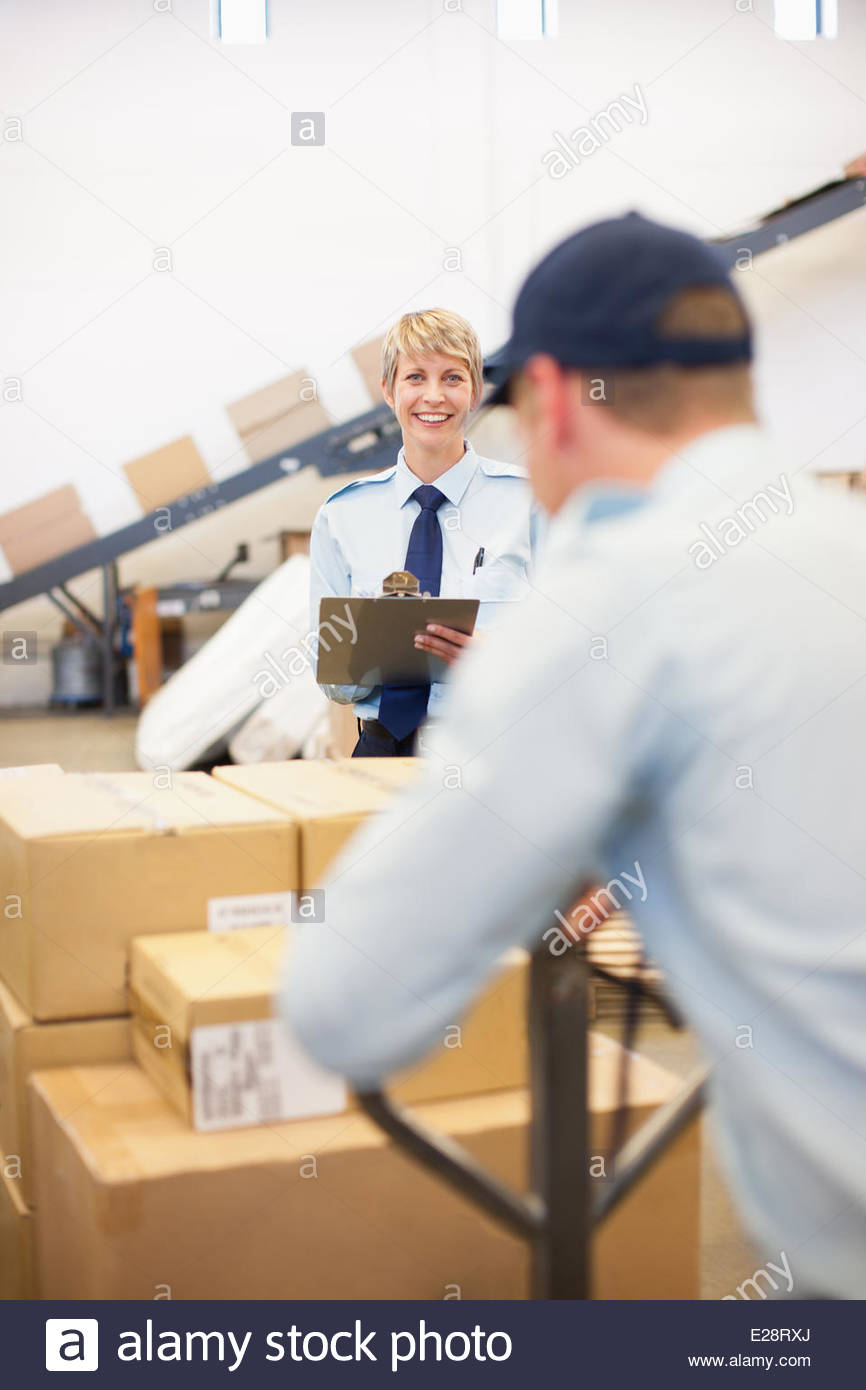 Worker moving boxes on hand cart in shipping area - Stock Image