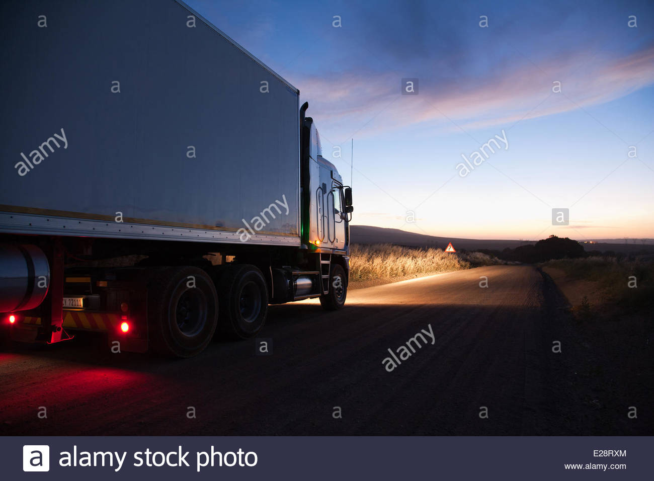 Semi-truck driving on dirt road - Stock Image