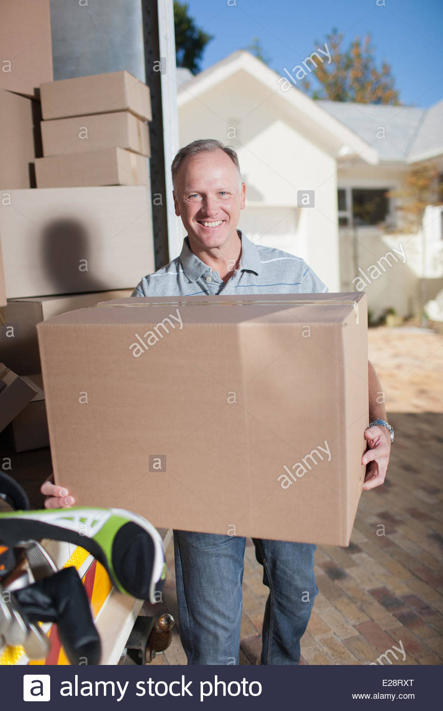 Smiling man carrying box from moving van - Stock Image
