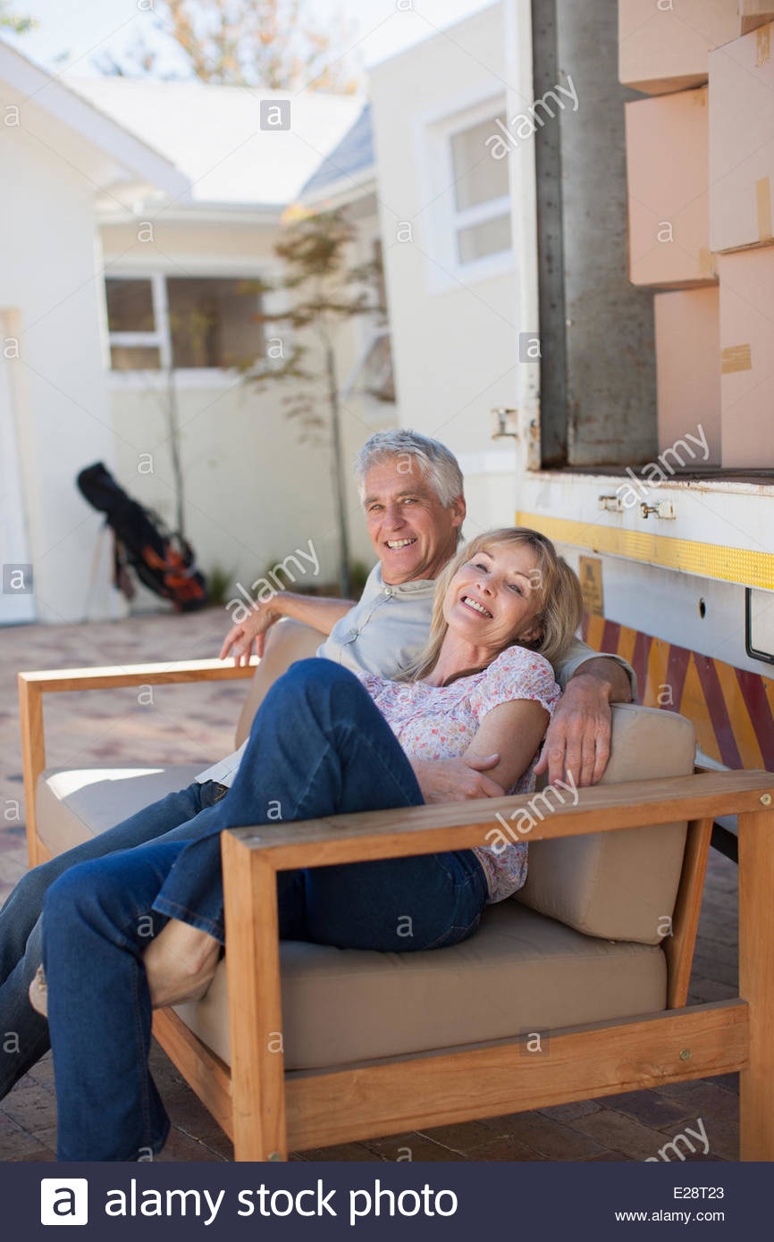 Couple sitting on sofa beside moving van - Stock Image