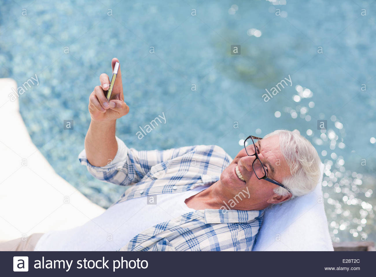 Senior man using cell phone at poolside - Stock Image