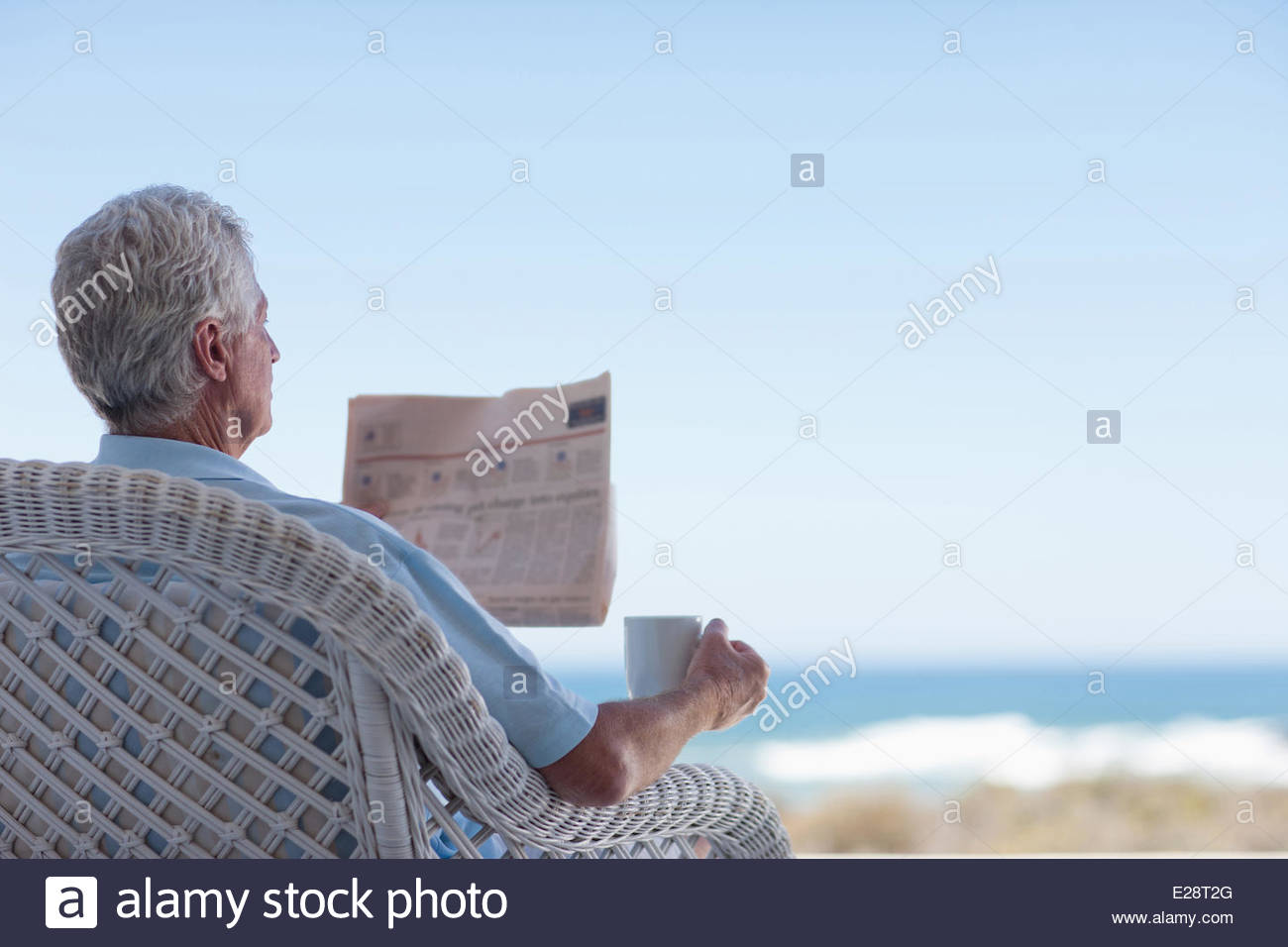 Senior man with coffee and newspaper on beach patio - Stock Image