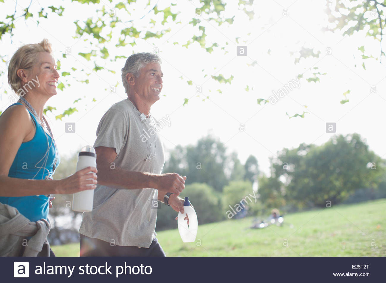 Couple jogging together with water bottles - Stock Image