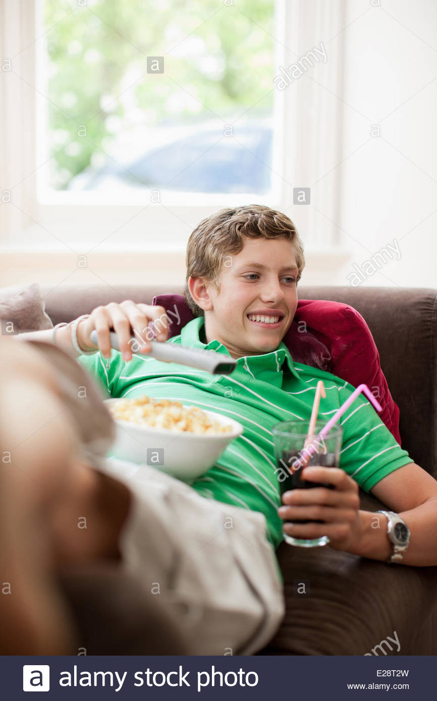 Teenage boy with snacks holding remote control - Stock Image