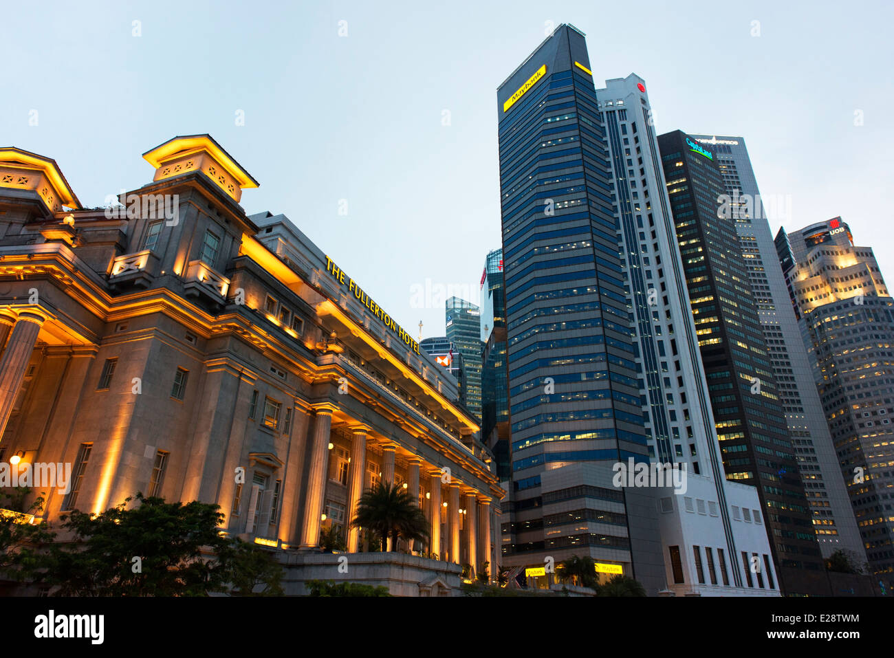 The Fullerton Hotel lit up at dusk with the business district's high rises beyond. - Stock Image