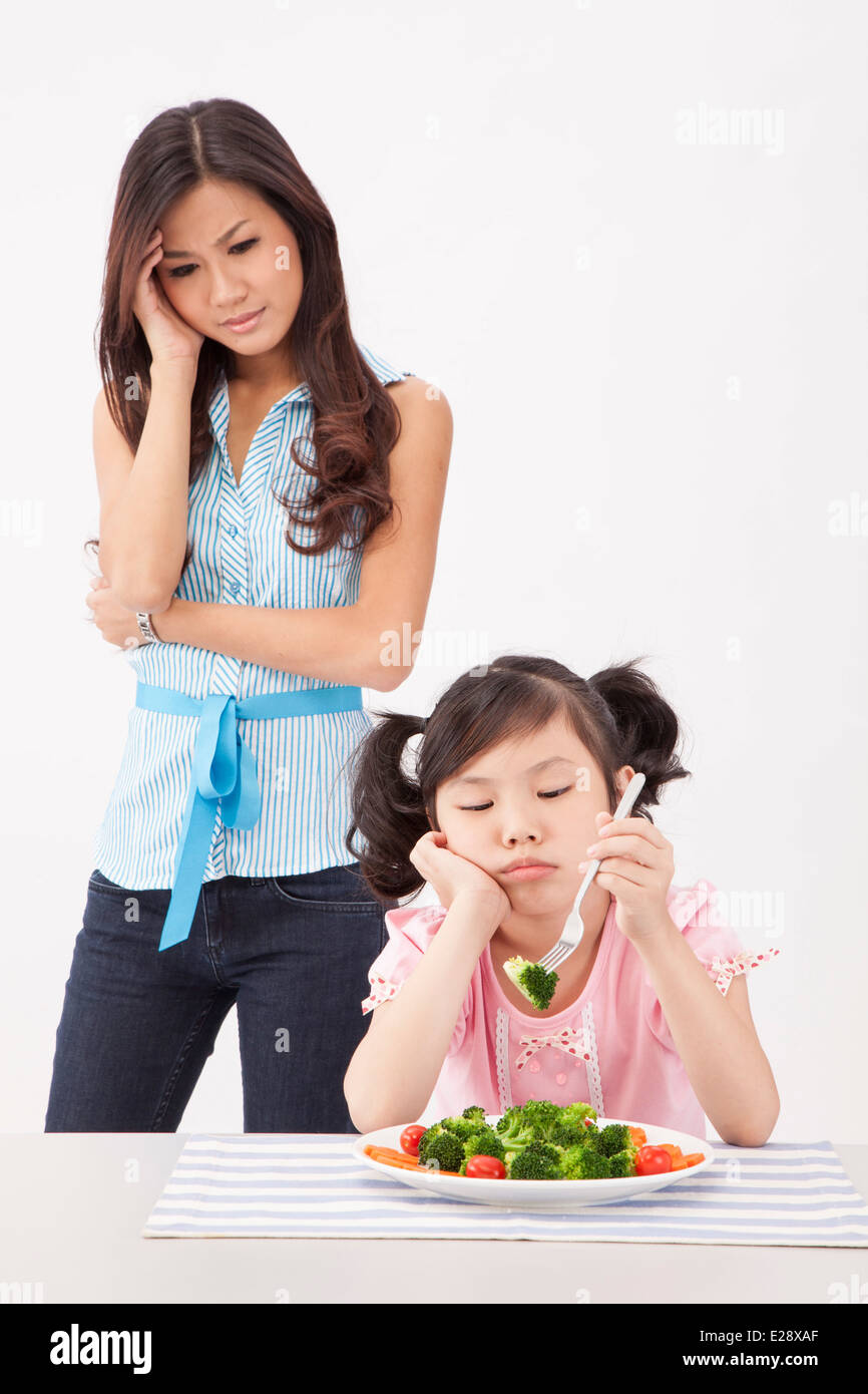 Young mother worries kid doesn't like to eat vegetables - Stock Image