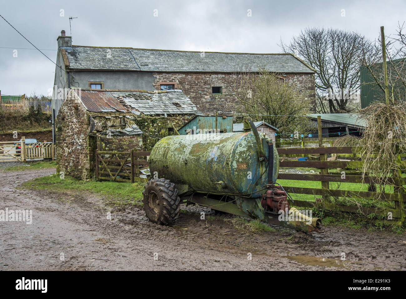 Slurry tanker and farm buildings, Cumbria, England, March - Stock Image