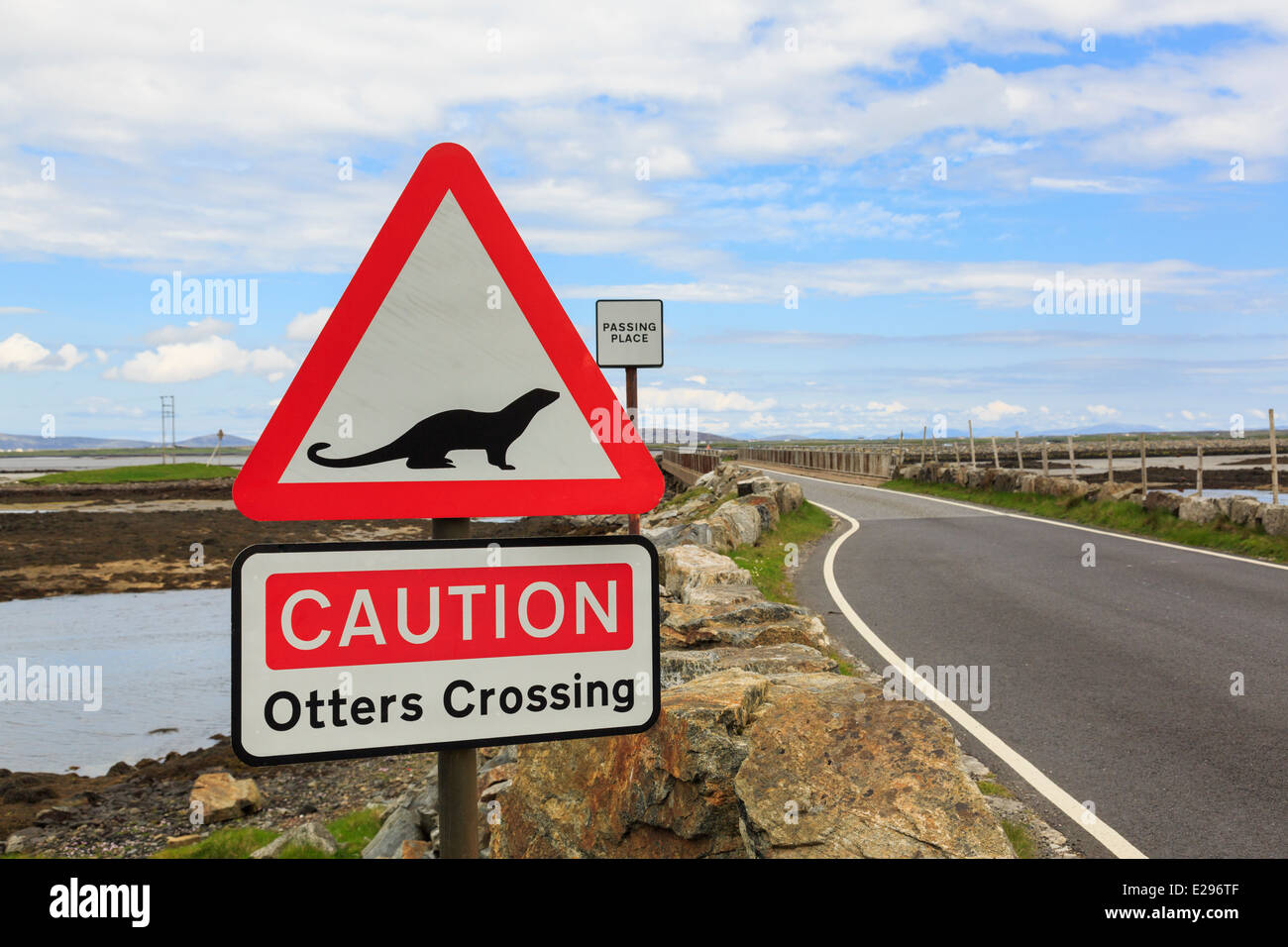 Caution Otters Crossing red triangle road sign by causeway from Benbecula to North Uist Outer Hebrides Western Isles - Stock Image