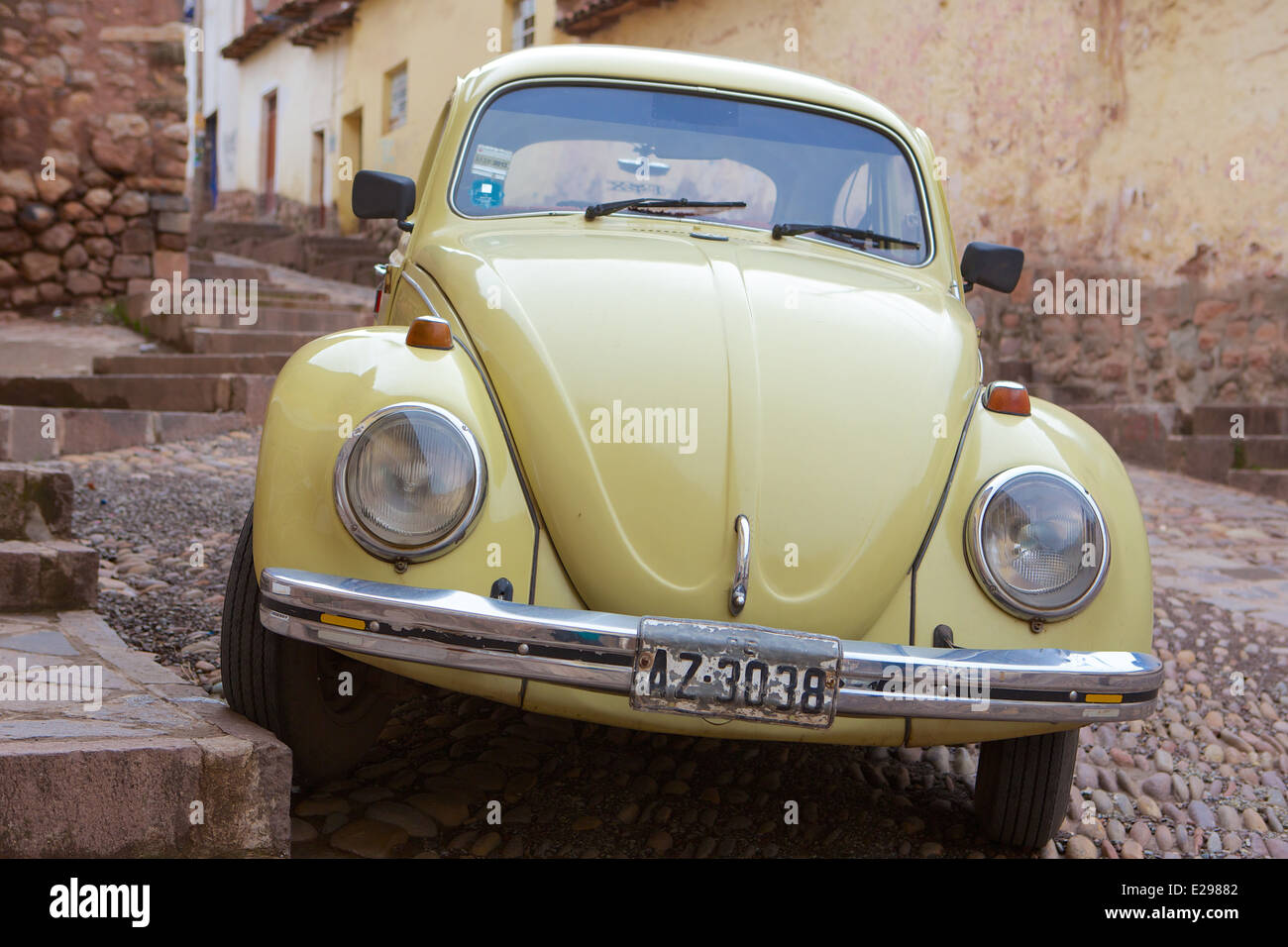 A pretty street scene with yellow vw bug on a steep street in Cusco, Peru, ancient seat of the Inca Empire high - Stock Image