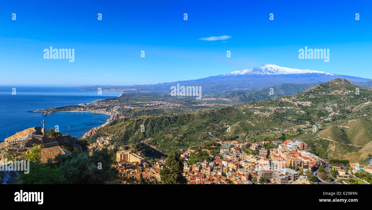 View of Mount Etna covered of snow, city of Taormina and coastline Stock Photo