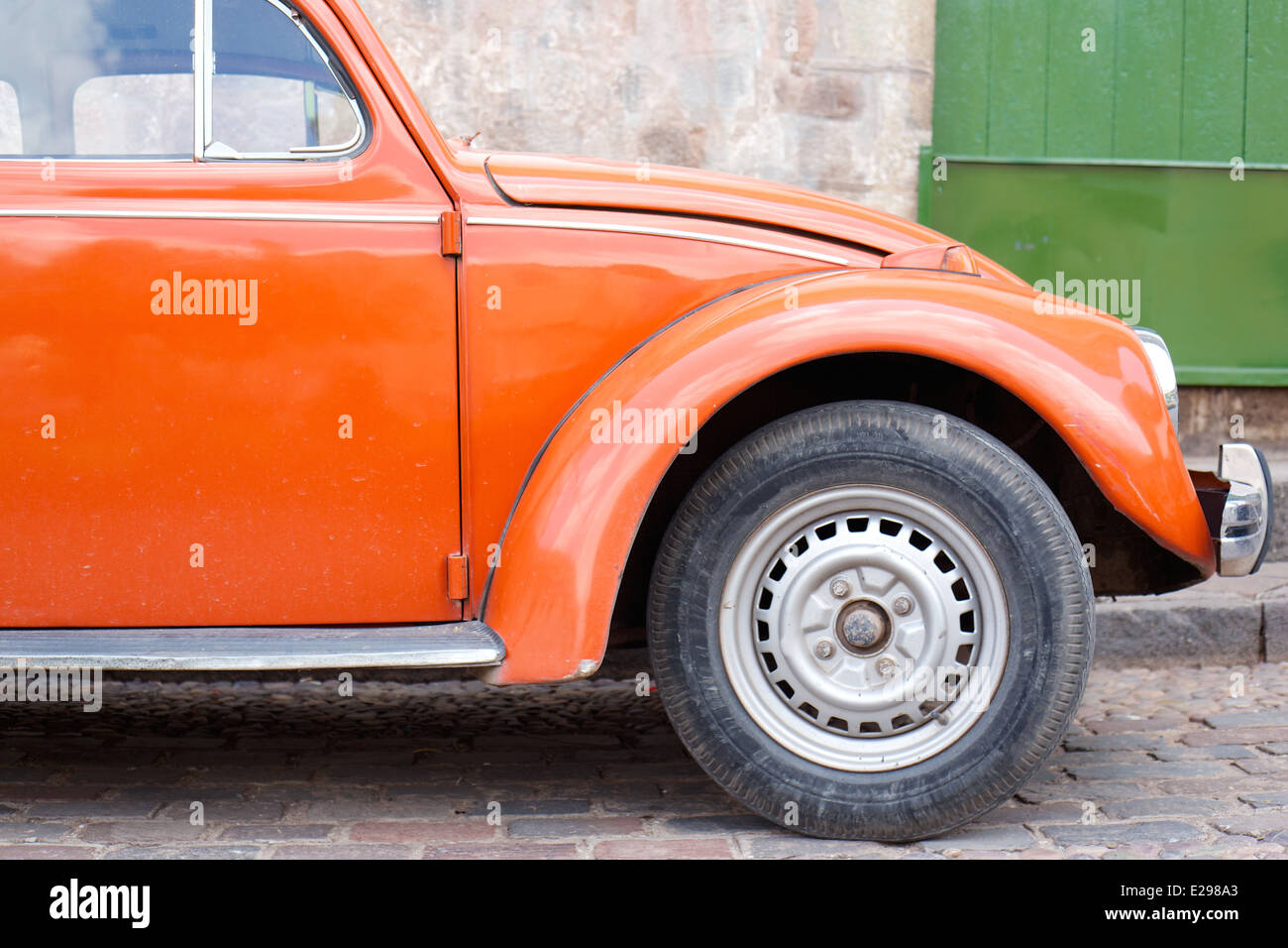 A pretty street scene with orange VW bug Cusco, Peru, the ancient seat of the Inca Empire high in the Andes. - Stock Image