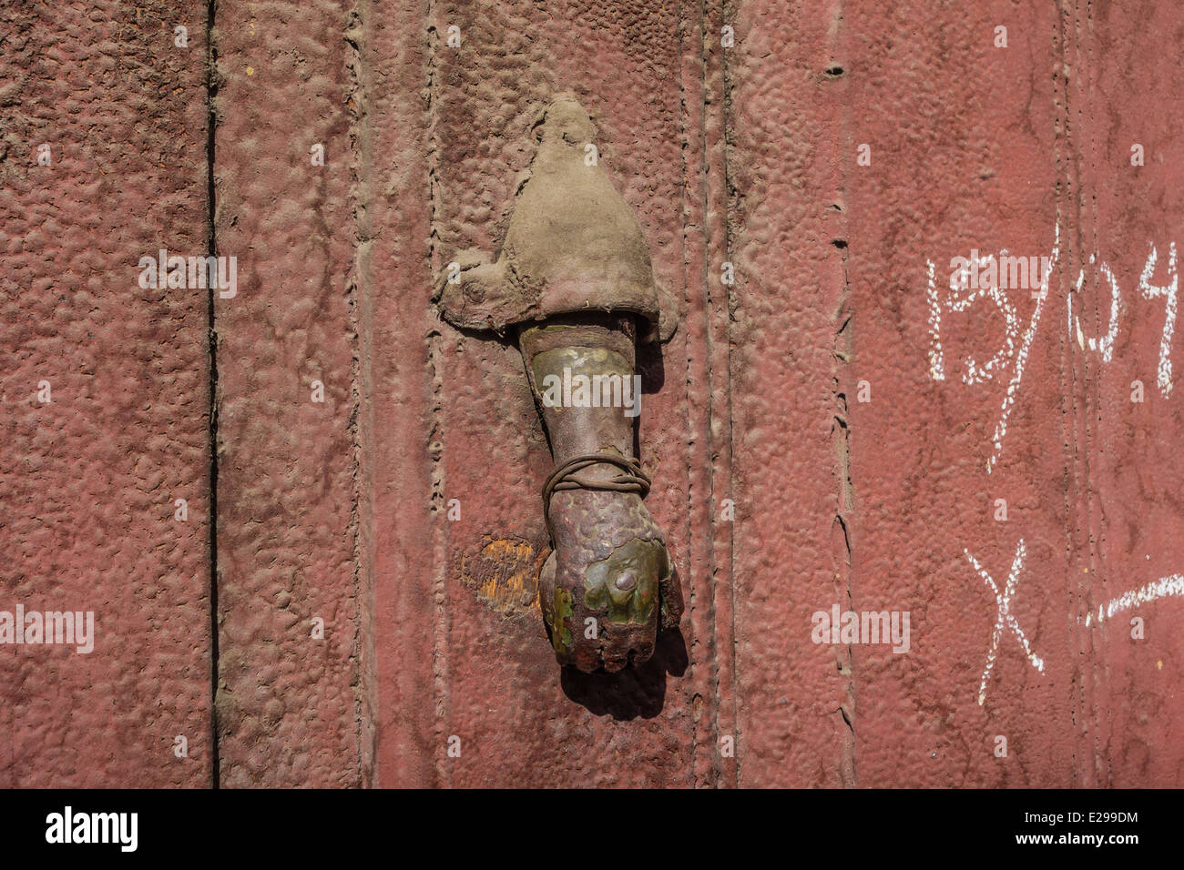 Antique metal door knocker that is well worn on a weathered door in the central part of Sucre, Bolivia - Stock Image