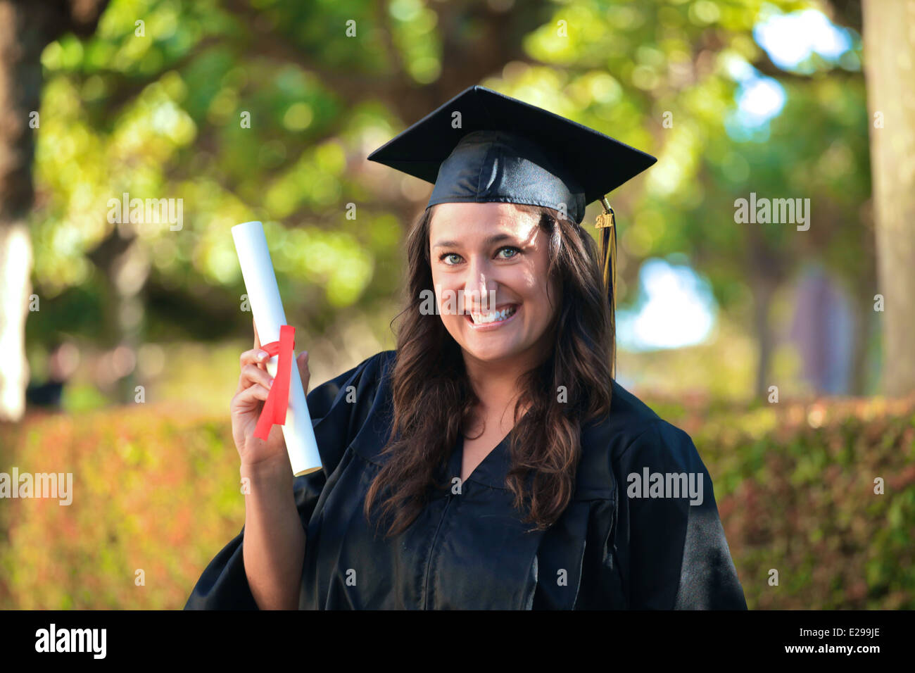 A beautiful girl with brown hair and blue eyes wearing a college graduation cap and gown smiles and holds her diploma - Stock Image