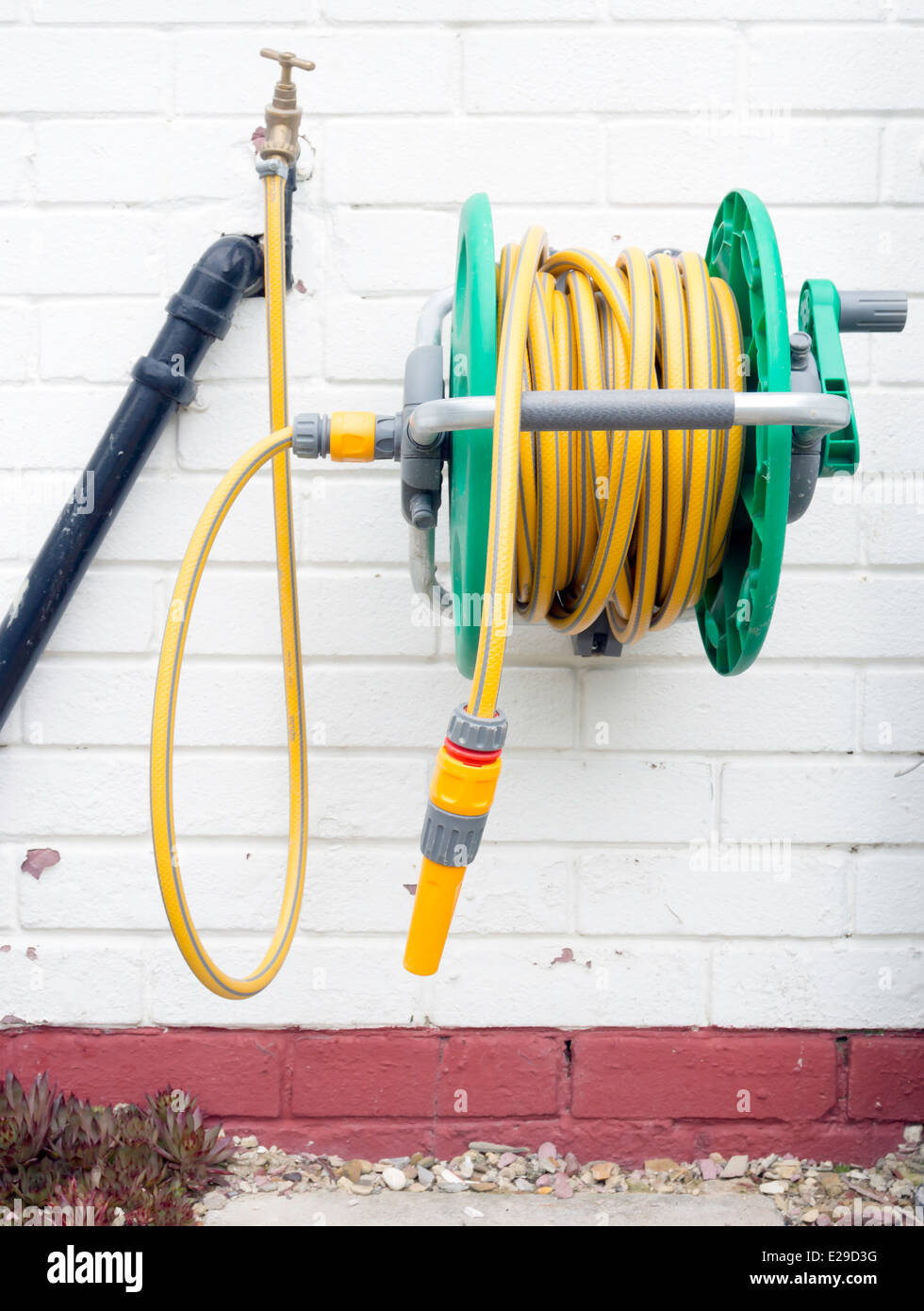 A Garden Hose Reel With Yellow Kink Resisting Hose Wall Mounted For  Convenient Deployment
