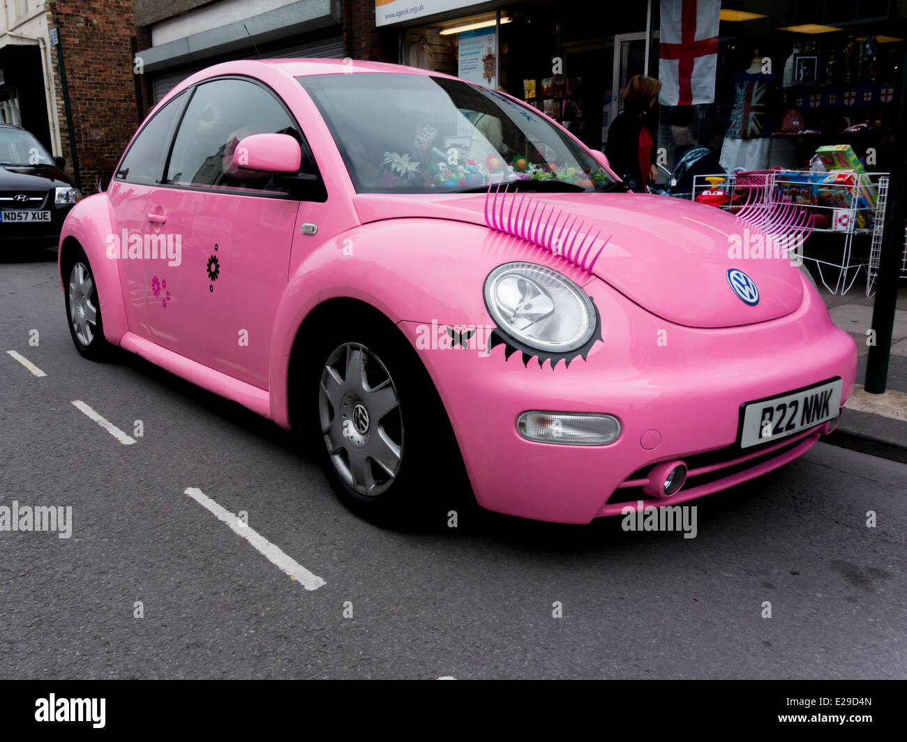 Modern Volkswagen Beetle car in exaggerated 'girly' colours bright pink with false eyebrows over the headlights - Stock Image