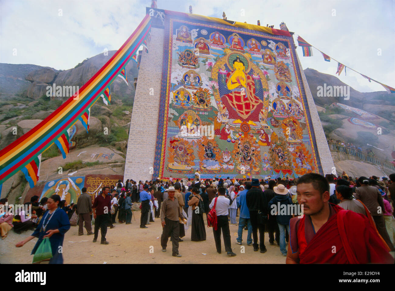 "A Tibetan Monk walks by a giant ""Thangka,"" a painted or embroidered Buddhist banner at Sera Monastery, Lhasa, Tibet Stock Photo"