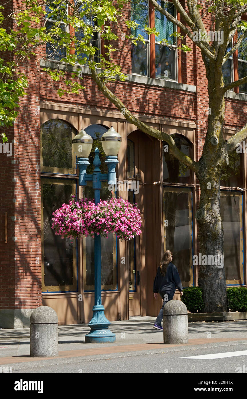 Woman walking past an old brick building in downtown Bellingham, Washington state, USA - Stock Image