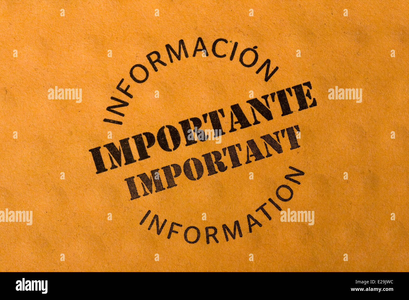 'IMPORTANT INFORMATION' stamp written bilingually in English and Spanish on brown dimpled paper - Stock Image
