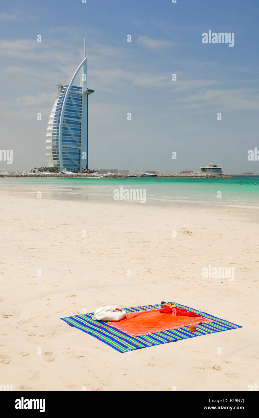 United Arab Emirates, Dubai emirate, Jumeirah, towel on the beach of Jumeirah Beach with in the background the Burj - Stock Image
