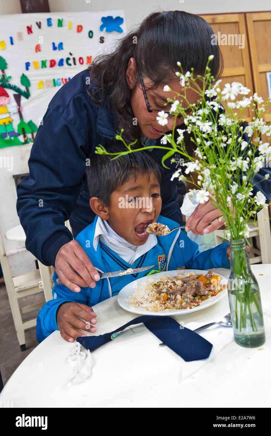 Peru, Cuzco Province, Cuzco, educator and child having lunch in one of the restaurants of the Ninos Unidos Peruanos - Stock Image