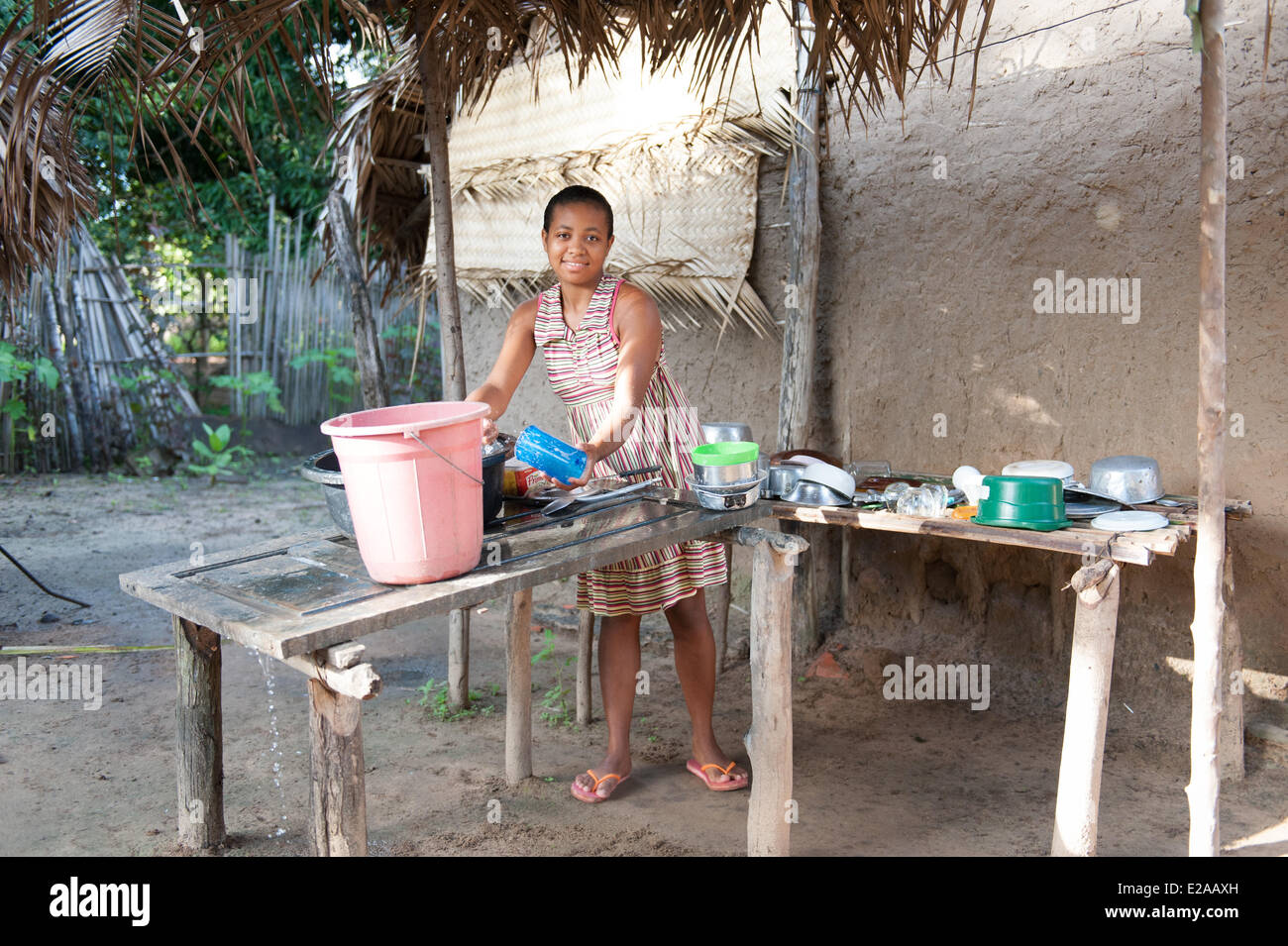 Young woman cleaning dishes. The water must be manually pumped. Streets, villages and people in Codó, Maranhao, - Stock Image