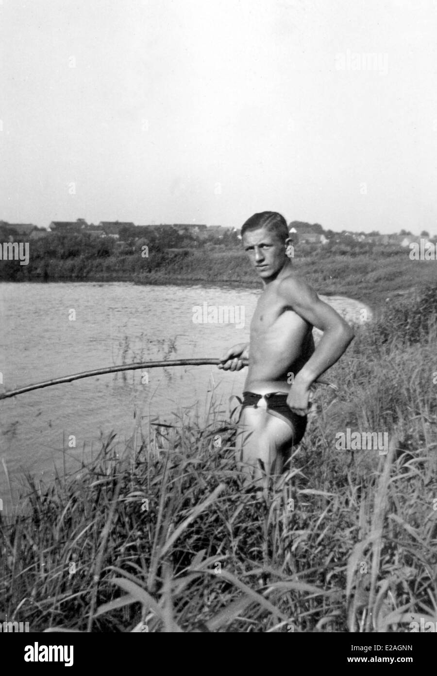 Youth camp at the river Oder in 1937 - young man fishing. - Stock Image