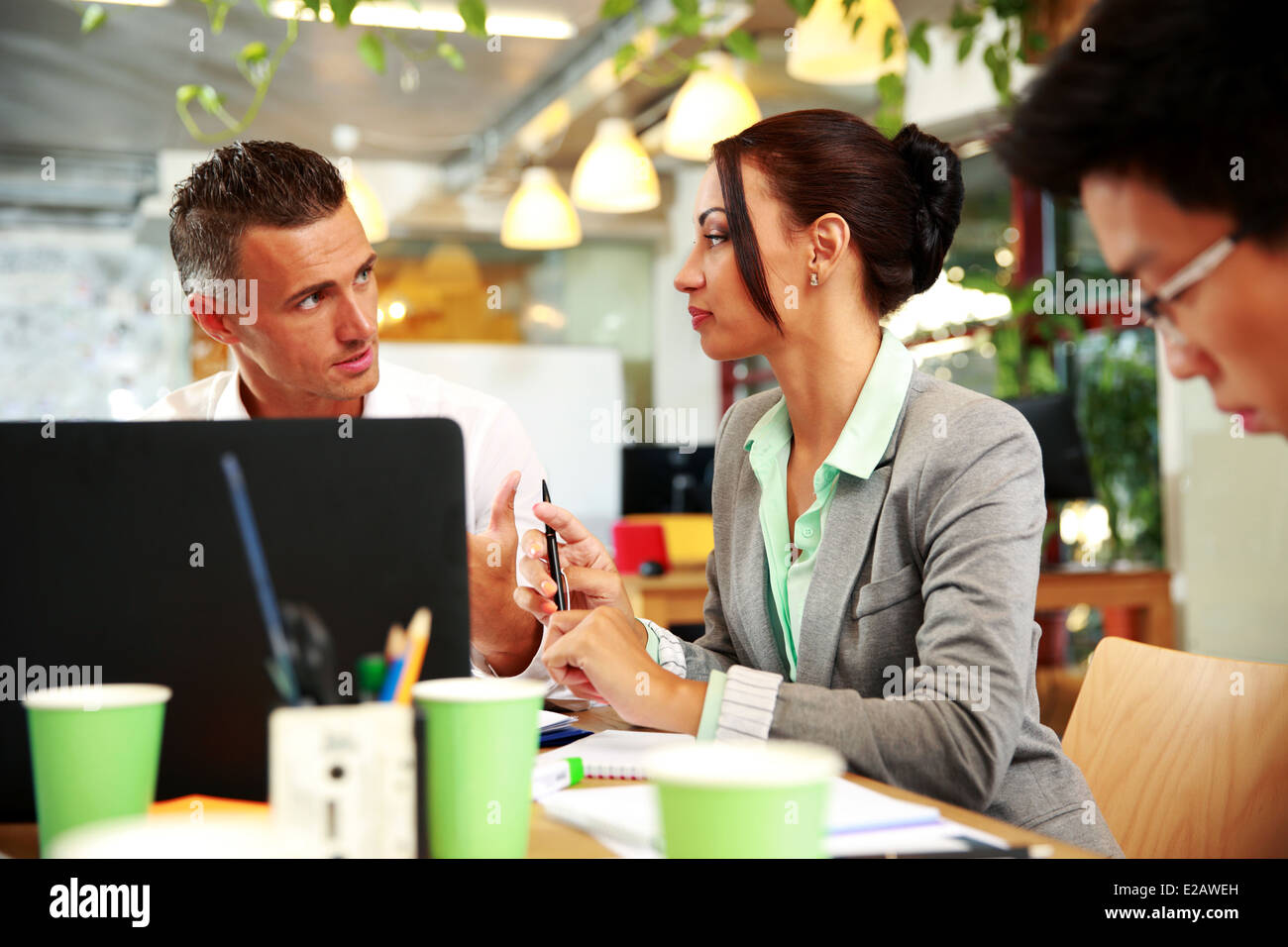 Business people having meeting around table in office - Stock Image