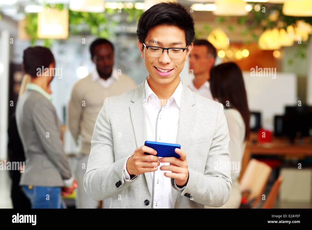 Portrait of a happy businessman using smartphone in front of colleagues - Stock Image