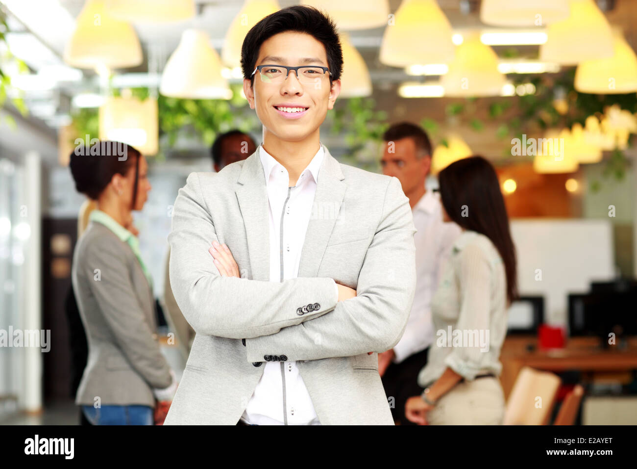 Portrait of smiling businessman with arms folded standing in front of colleagues - Stock Image