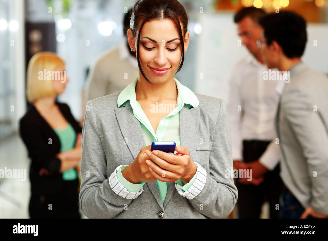 Portrait of a happy businesswoman using smartphone in front of colleagues - Stock Image