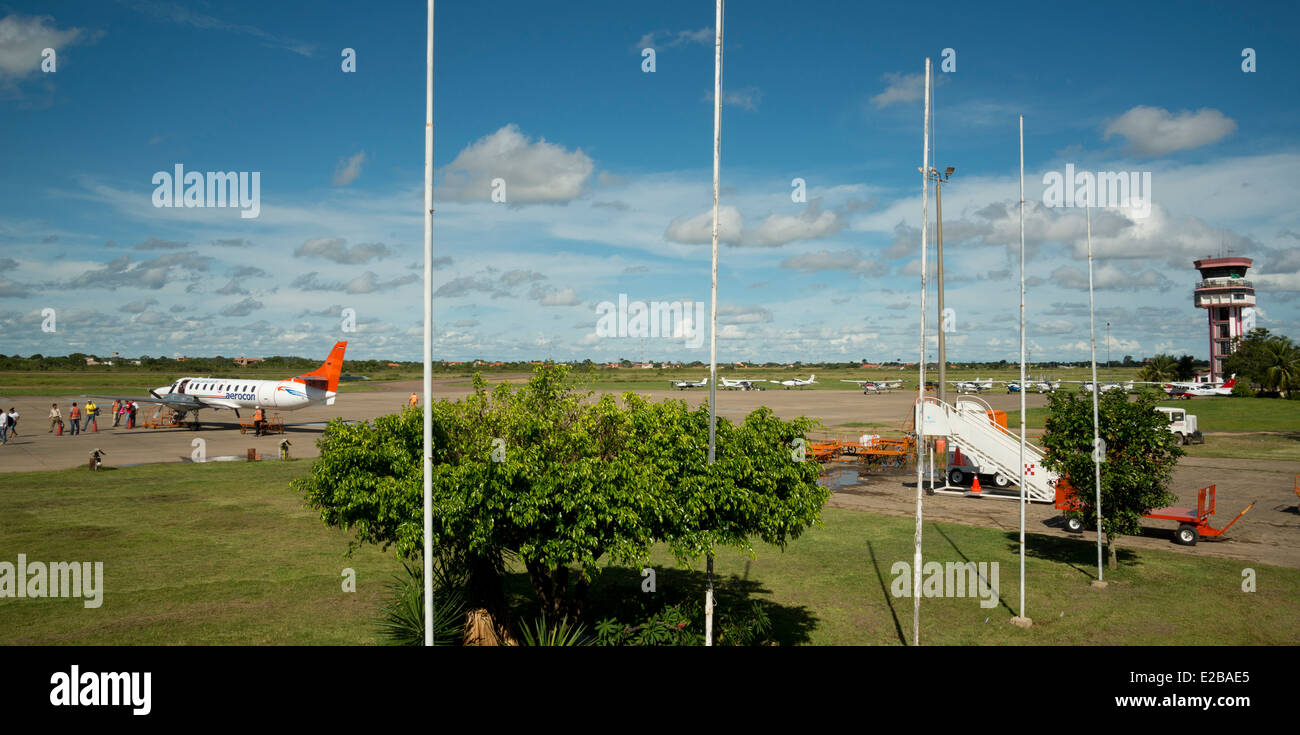 Trinidad Airport in Bolivia. Propeller plane on runway with passengers disembarking and luggage being handled. - Stock Image