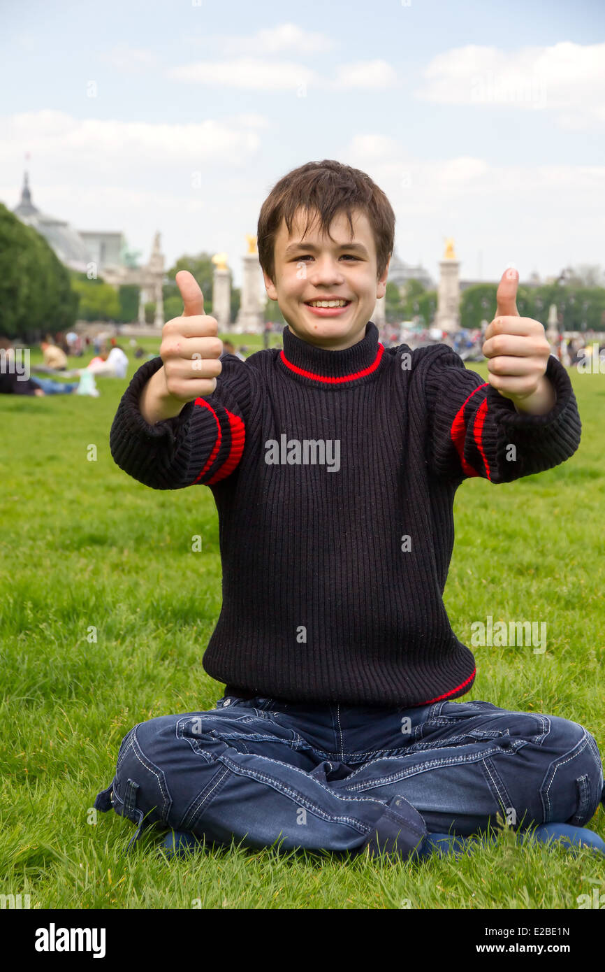 Cheerful teenager shows thumb up sitting on the Esplanade des Invalides in Paris , France - Stock Image