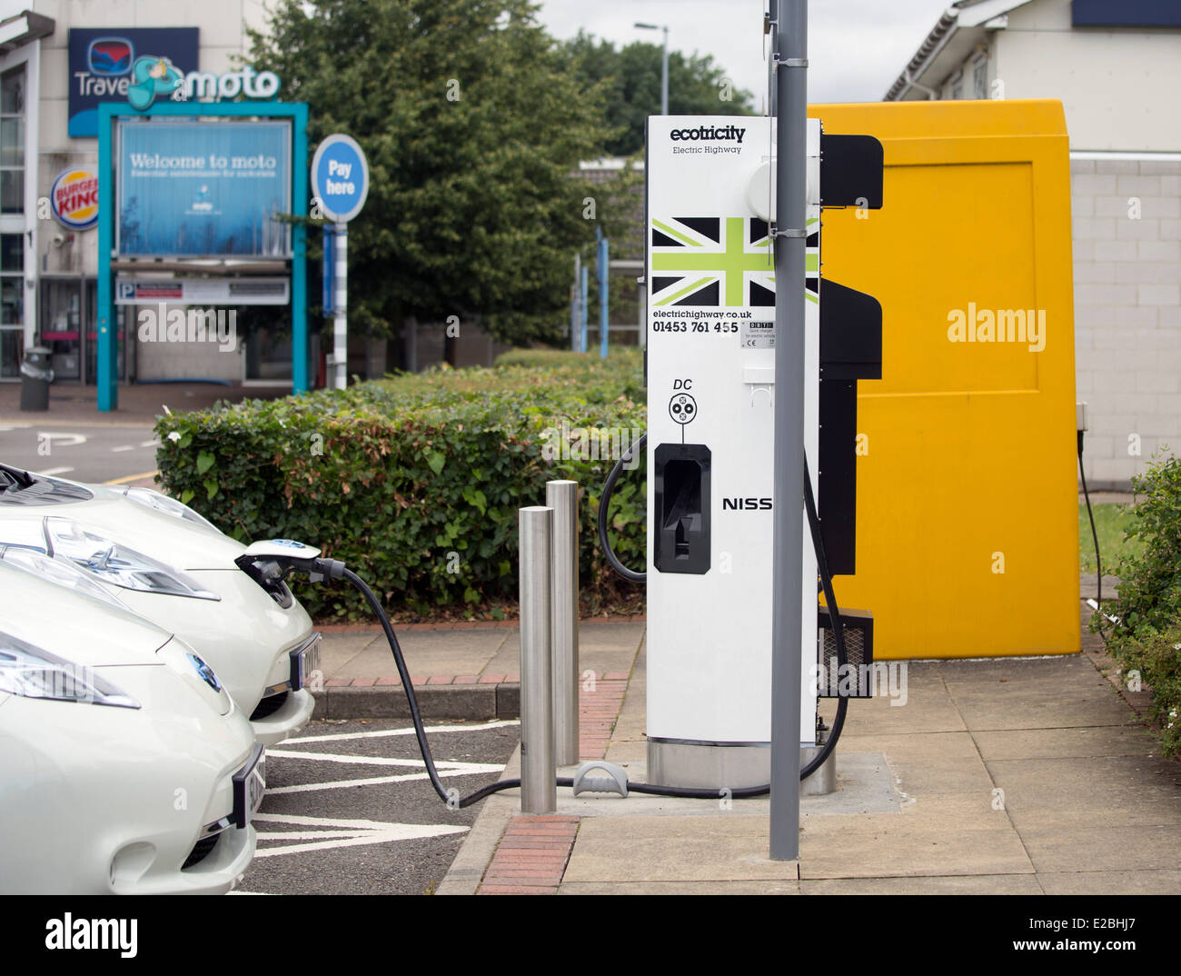 Pair of Electric cars Nissan Leaf on charge at Heston Services. - Stock Image