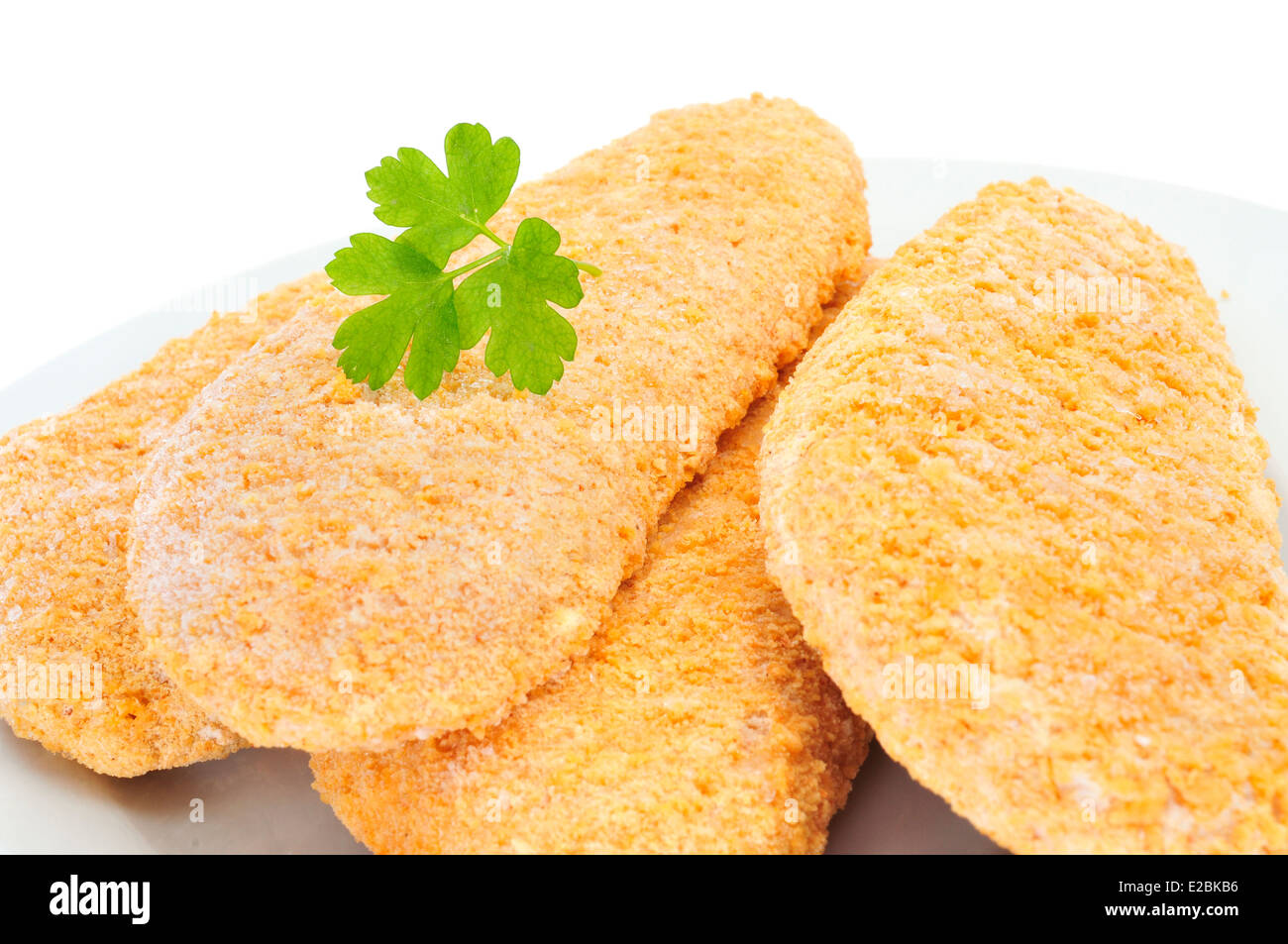 closeup of a plate with some pieces of frozen breaded fish on a white background ready to be cooked Stock Photo