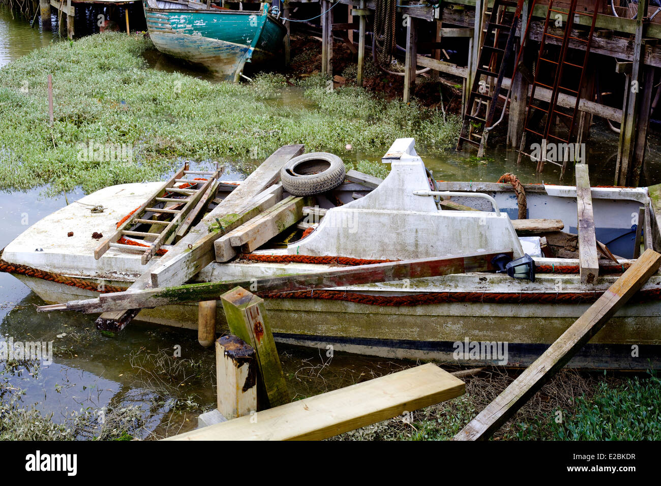 Sinking Boat with junk aboard. - Stock Image