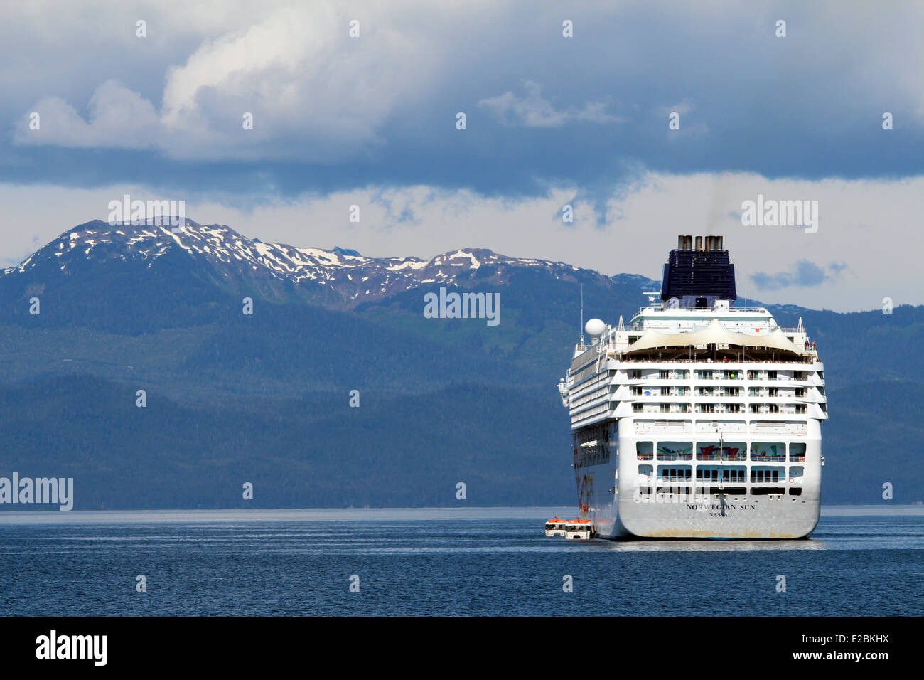 Cruise ship anchored outside Icy Strait Point Alaska snow capped mountains in the background. - Stock Image