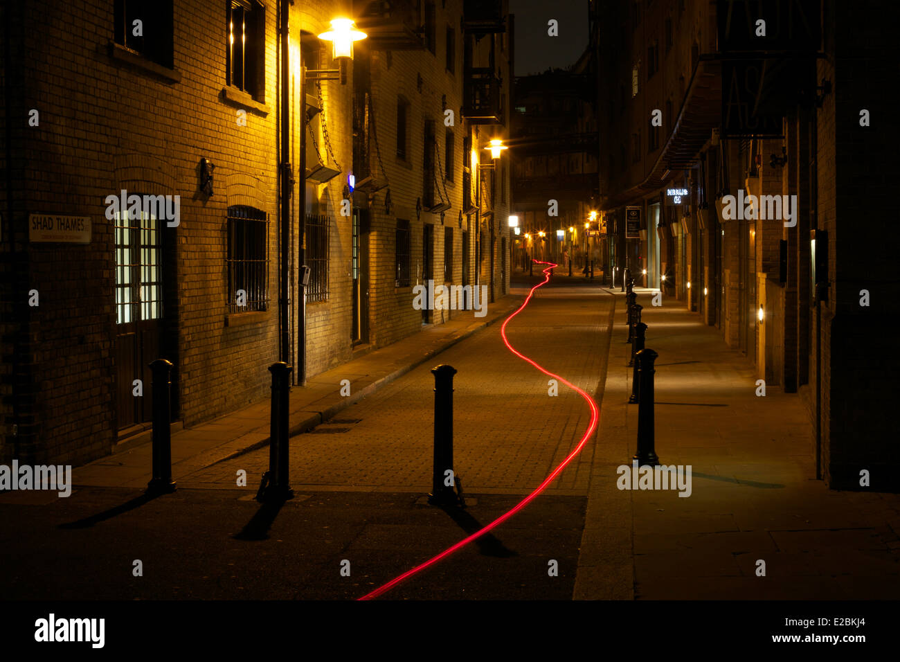 Shad Thames London at night with red travel line. - Stock Image