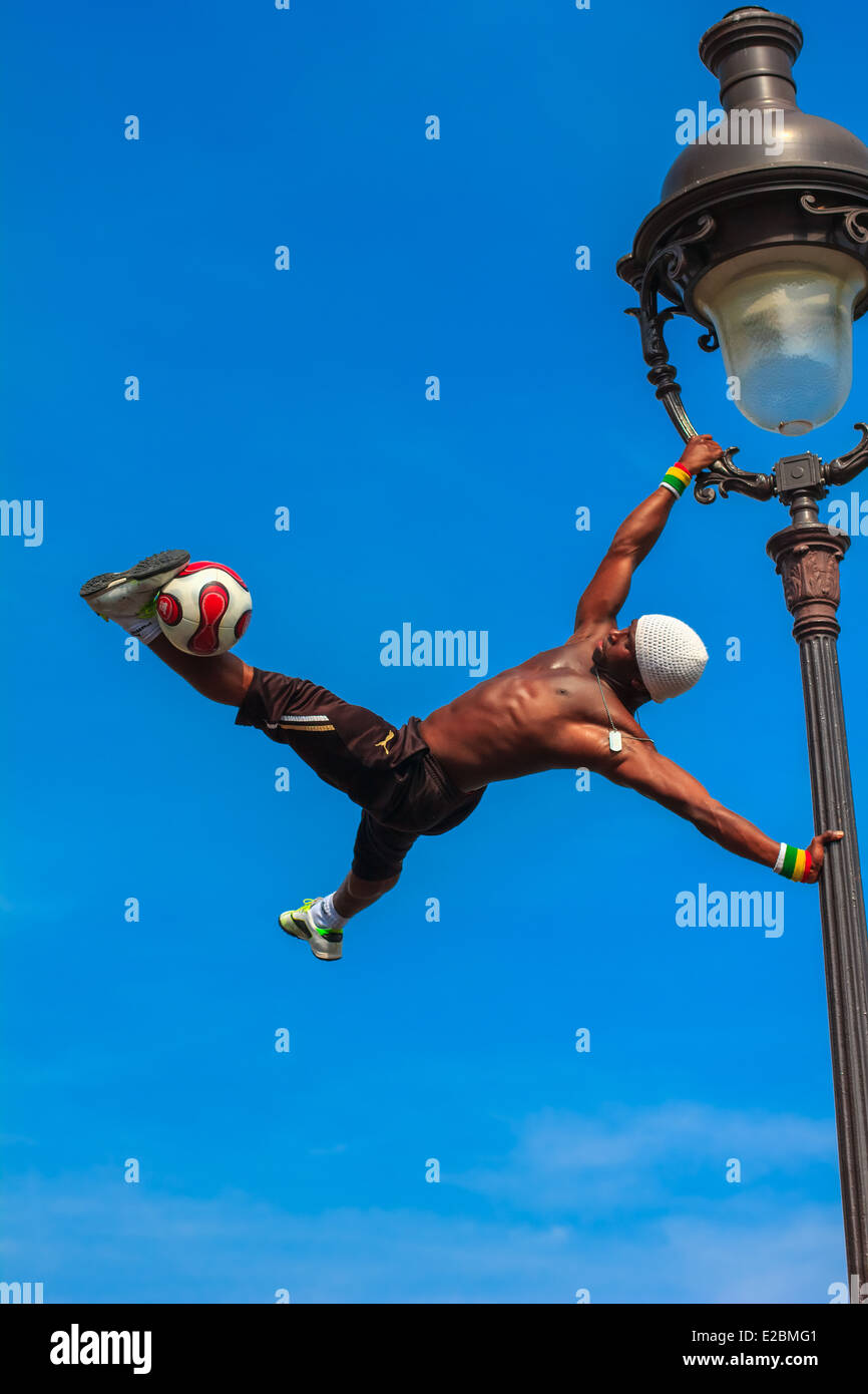 Incredible Football Freestyle Iya Traore hanging on Lamp Post and juggling a Soccer Ball in front of Sacre Coeur - Stock Image