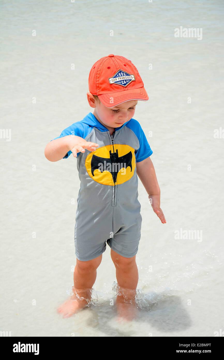 Little boy in the shallow surf wearing his batman onesie Stock Photo