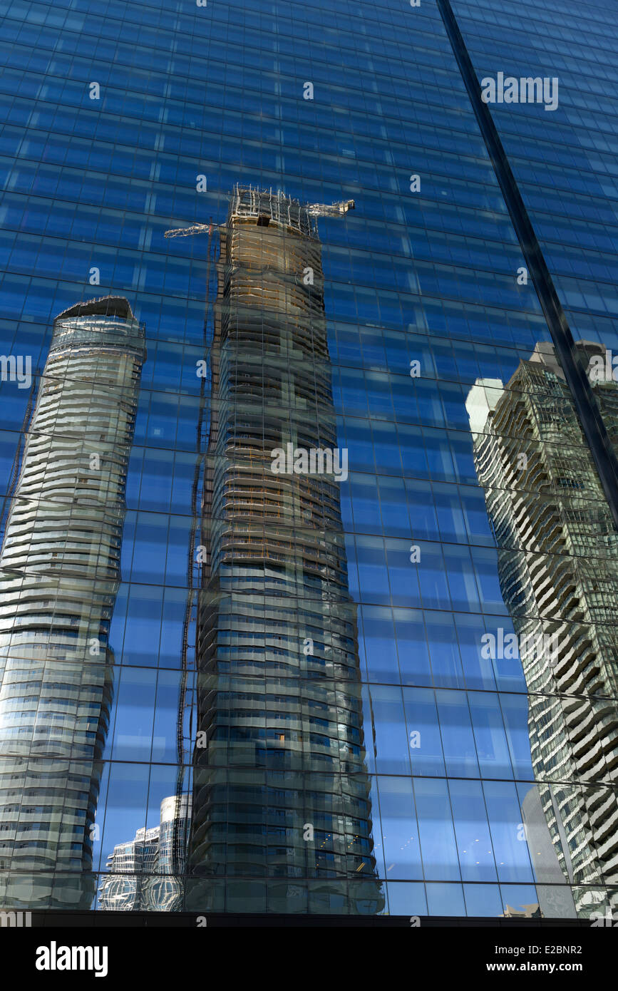 Reflections of new condominium development in blue glass of PwC tower office building Toronto - Stock Image