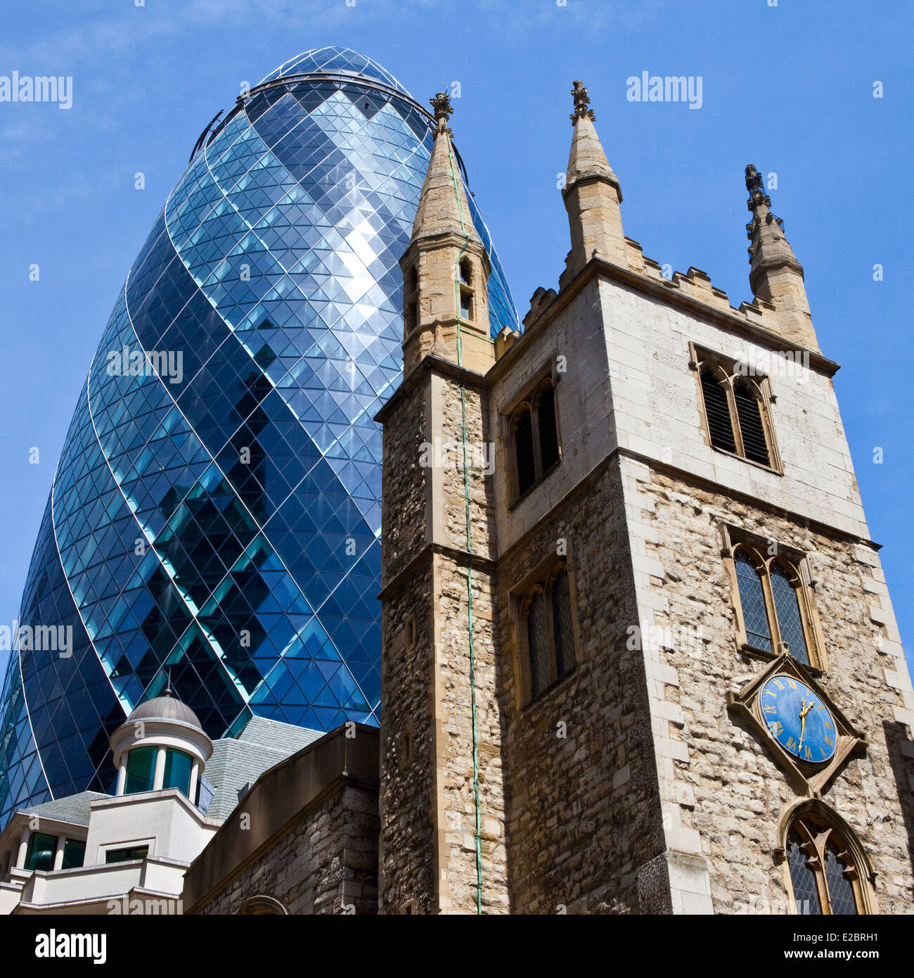 The historic St. Andrew Undershaft Church with 30 St. Mary Axe towering above it in the City of London. Stock Photo