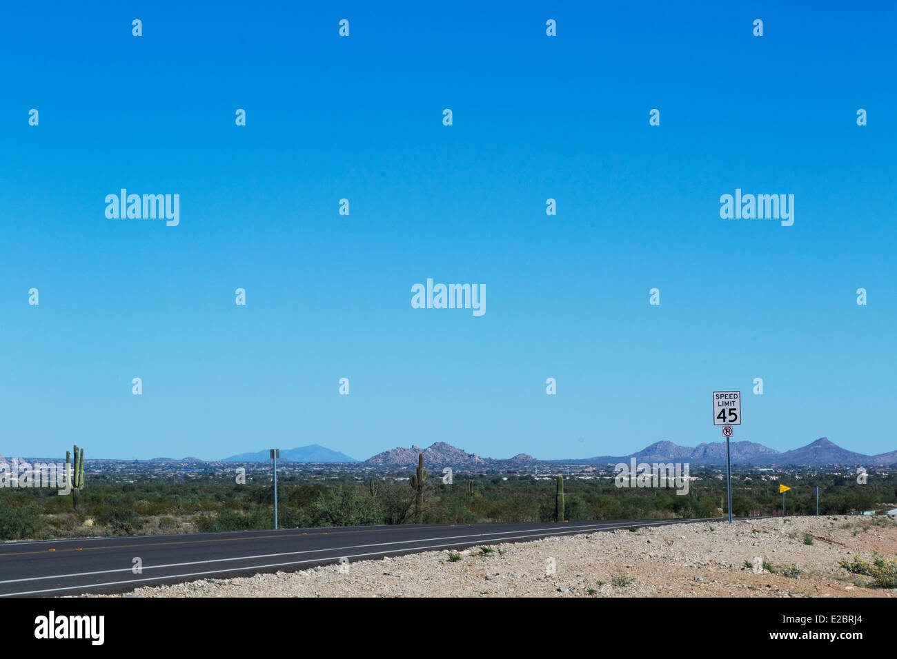 Desert road with speed limit and mountains Stock Photo