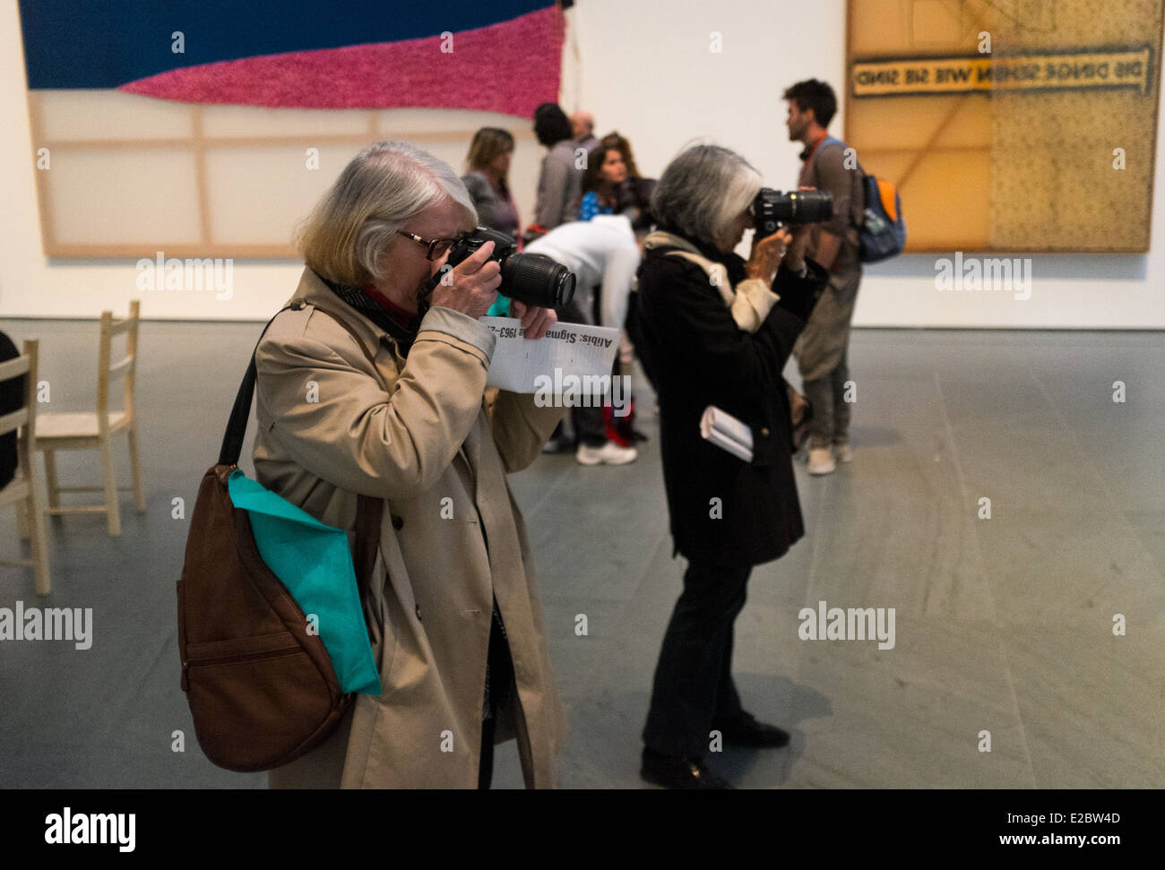 Two women take photographs at an exhibit in the Museum of Modern Art in New York. - Stock Image