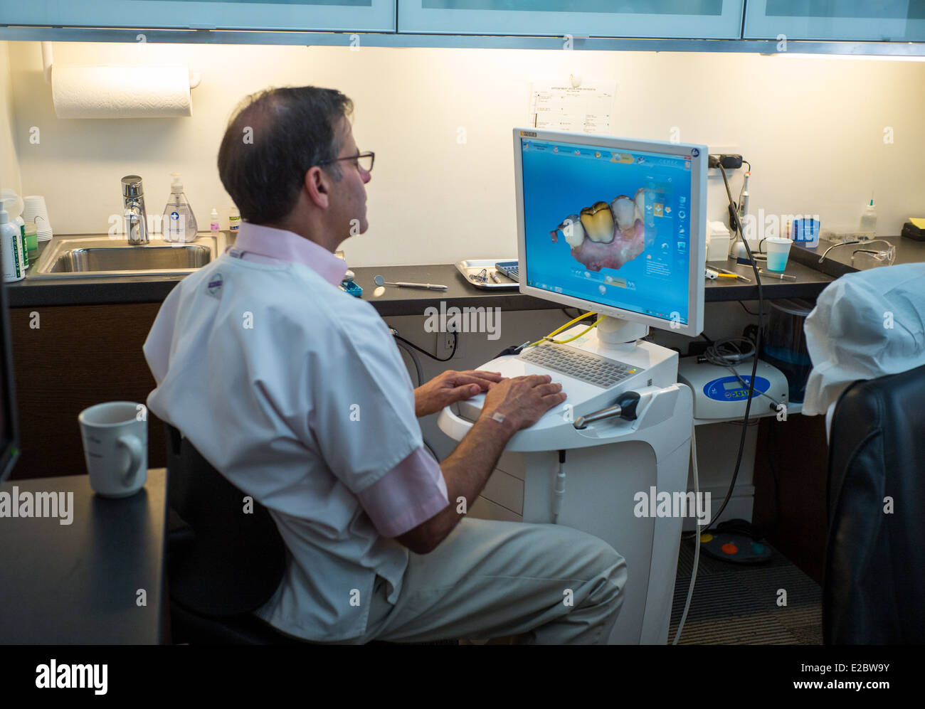 Dentist Dr. Marc Beshar works on a 3-dimensional computer generated replacement crown manufactured by a German company. - Stock Image