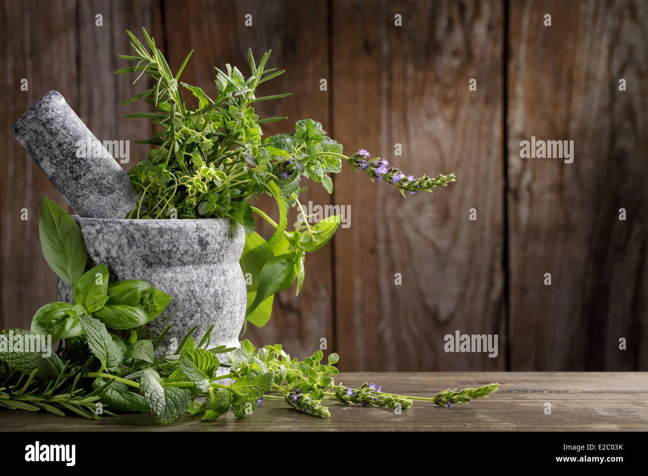 herbs in mortar on wooden background - Stock Image
